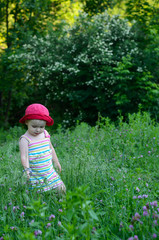 cute little girl playing in the green field