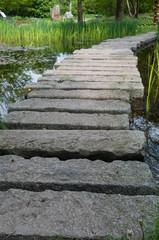Steinbrücke auf einem Teich im Park