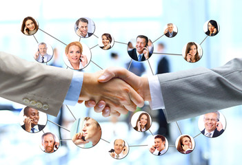 business people handshake with company team in background