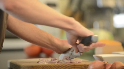 Home cook chopping onions on a wooden board