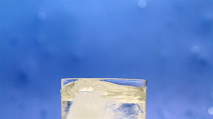 Ice cubes dropped into glass of water. Filmed at 50 fps.