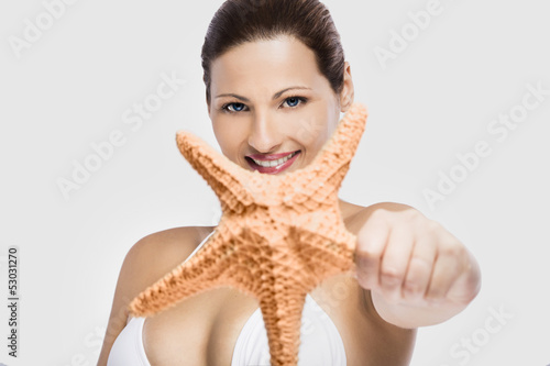 Beautiful woman holding a starfish