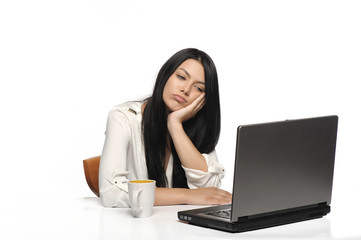 Bored business woman working on laptop