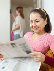 mature woman reads newspaper during  daughter cleans at home