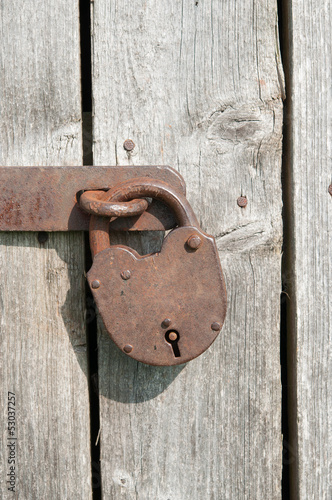Old rusty padlock on a wooden door