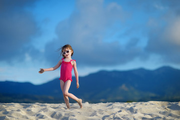 Adorable little girl playing on a sandy beach