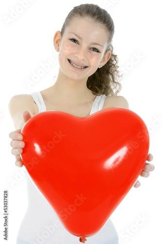 Lachender Teenager mit Herz-Luftballon