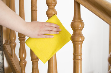 cleaning wooden railing with yellow cloth horizontal