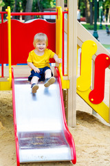 Adorable kid going down the playground slide