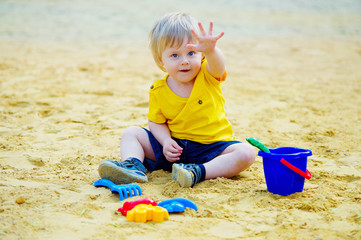 Cute little boy playing with his toys in the sandbox