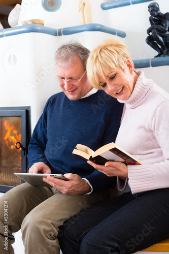 Seniors at home in front of fireplace