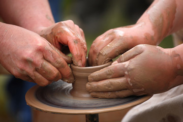 hands of a potter, creating an earthen jar on the potter's wheel