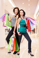 Young adult girls with shopping bags at shop