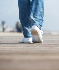Rear view woman walking in comfortable white shoes outdoors