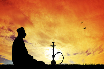 Arab with hookah at sunset