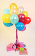 Many bright balloons and many gifts on light background