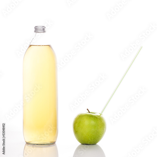 juice in a glass bottle and green apple