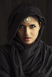 Indian beautiful Muslim girl portrait on dark background.