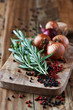 Rosemary, peppercorns and onions on chopping board