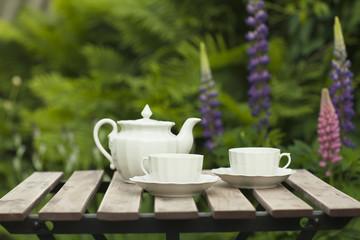 Белые чашки и чайник на столике в саду