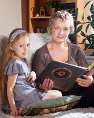 Lovely little girl  reading with her grandmother
