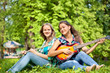 two girls playing guitar and flute in the park