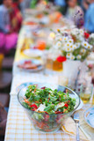Mixed green salad with carrot and tomatoes on picnic table