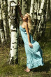 Beautiful blond woman in summer forest. flying dress