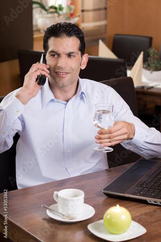 canvas print picture Geschäftsmann im Restaurant beim telefonieren