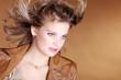 Hübsche junge Frau mit fliegenden Haare blickt