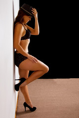 Woman in black underwear stand against wall