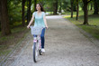 Young woman enjoying in bike ride in a park