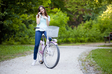 Young woman sitting on her bicycle and talking on the phone