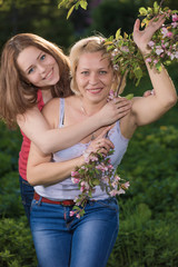 Mother and the daughter in blossoming to a garden