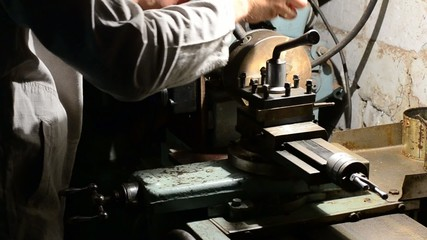 Man working on an old style lathe closeup