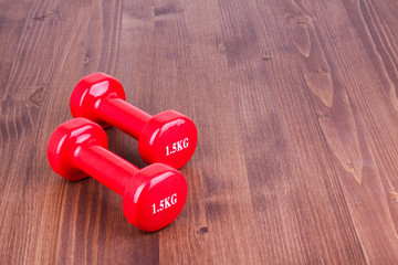 Fitness dumbbells on wood floor background