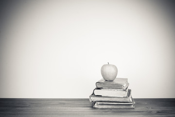 Apple, old books on table for vintage style background