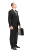 Full length portrait of a young businessman with briefcase looki