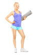 Full length portrait of a young female holding an exercising mat