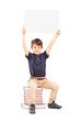 Happy school boy holding a blank panel above his head, seated on