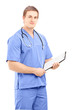Male medical doctor in a uniform holding a clipboard and posing