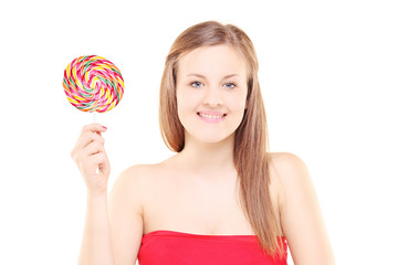 Pretty young girl holding a lollipop and looking at camera