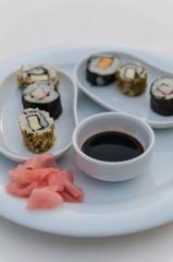 Ein Teller mit Sushi und Ingewer auf weisser Tischdecke
