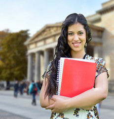 Portrait of happy student girl against street background
