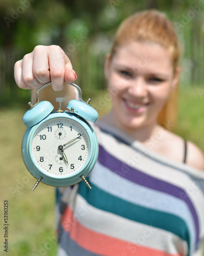 Teenage girl holding vontage clock outdoors with focus on clock