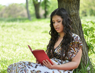 Woman reading book leaned against tree