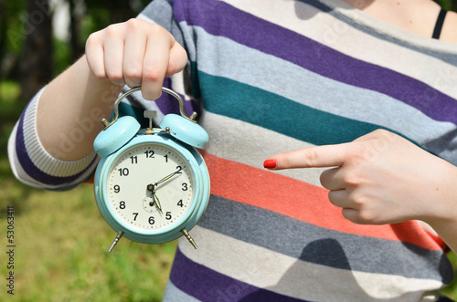 Woman hands pointing on old clock outdoors