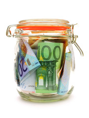 Money jar containing Euro notes isolated on white