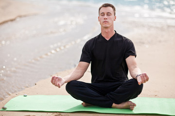 young man doing yoga on the beach