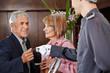 Senioren nehmen Schlüsselkarte von Hotelpage